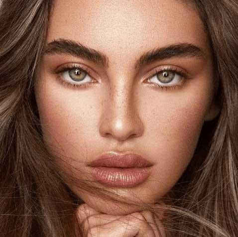 Beautiful woman with seductive green eyes and brow lamination looking at you