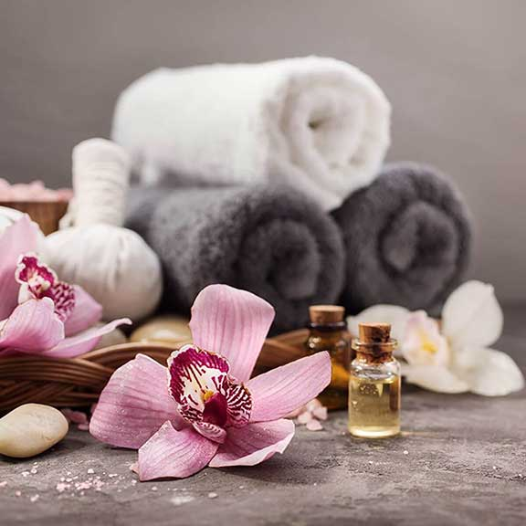 Pink orchid flowers, essential oils, white and grey towels