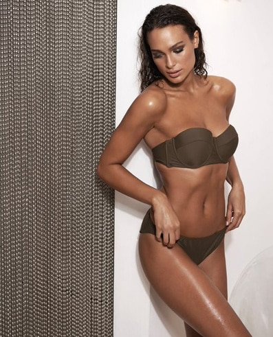 Tanned lady next to curtain